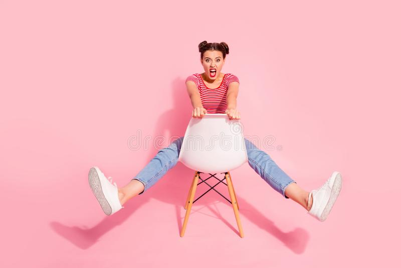 Nice-looking attractive glamorous lovely shine crazy girl wearing striped tshirt jeans sitting on chair having fun. Fooling isolated over pink pastel background royalty free stock photos
