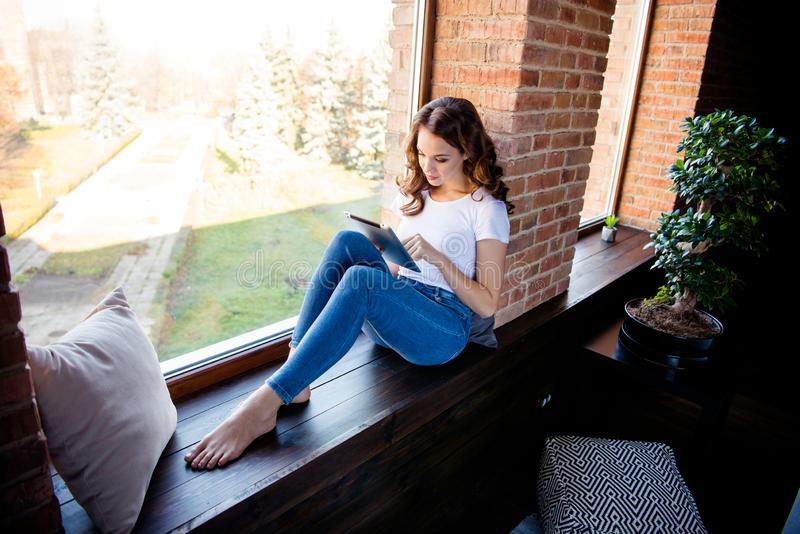 Nice-looking attractive lovely charming fit slim thin concentrated focused wavy-haired girl sitting on window sill. Reading ebook news at industrial loft wooden royalty free stock photography
