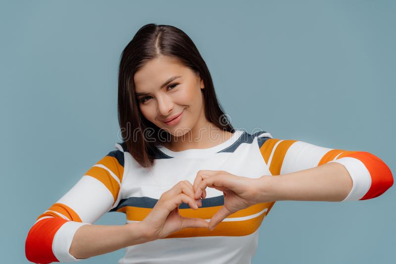 Nice looking brunette woman shows heart gesture, wears casual clothes, expresses love and sympathy, models over blue background. Romantic female demonstrates stock photography