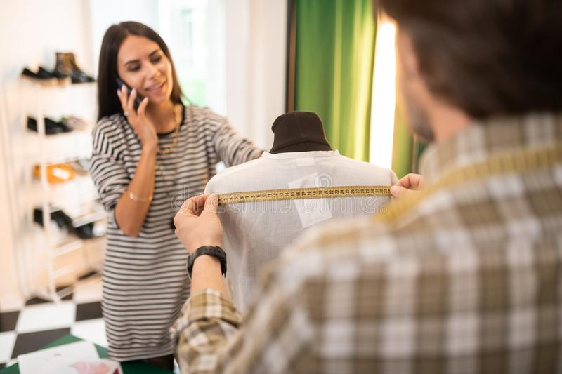 Nice-looking male fashion designer getting measurements of a white shirt royalty free stock photo