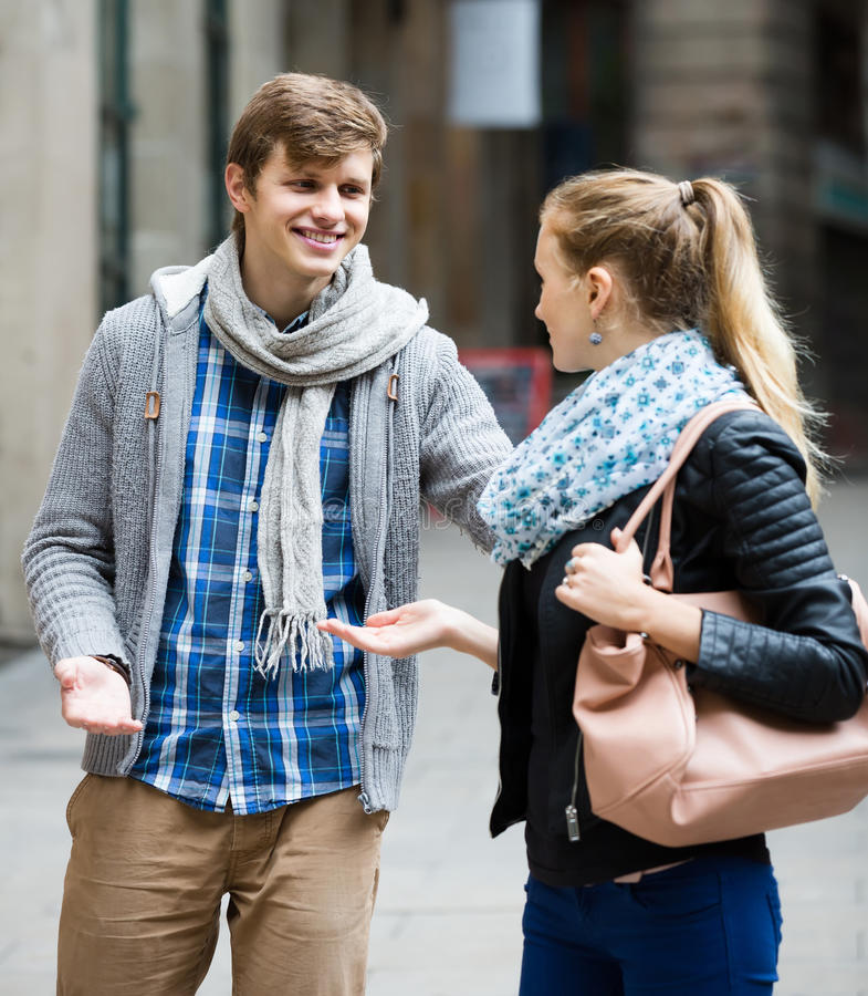 Nice-looking male student chasing pleased girl on outdoor date stock image