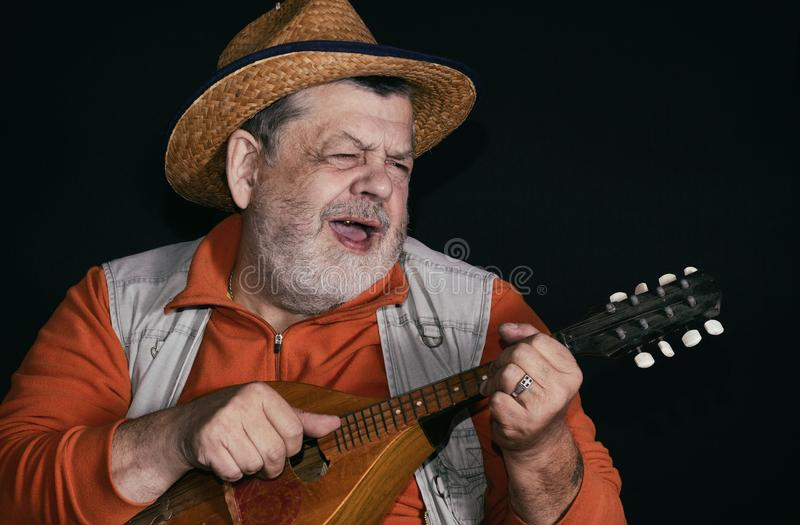 Low key portrait of senior musician with mandolin. Nice low key portrait of senior musician with mandolin playing and singing country music royalty free stock photography