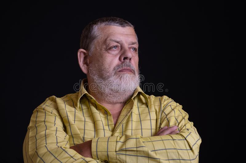 Portrait of a thoughtful Caucasian, bearded senior man in yellow shirt stock images