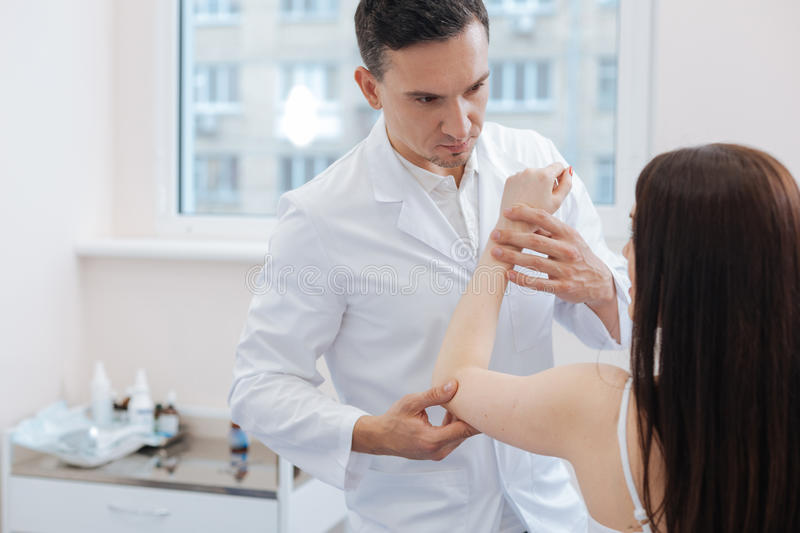 Nice male doctor holding his patients hand. Professional medical examination. Nice experienced male doctor holding his patients hand and examining it while stock image