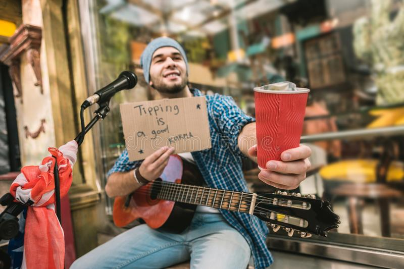 Nice male musician pleading for tips after play stock images