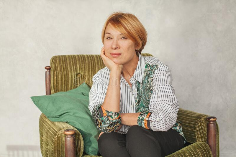 Nice mature woman with short ginger hair sitting on green armchair at home royalty free stock photography