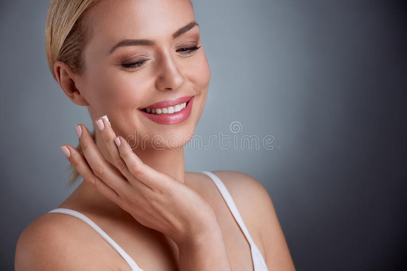 Nice middle aged woman applying face cream stock photography
