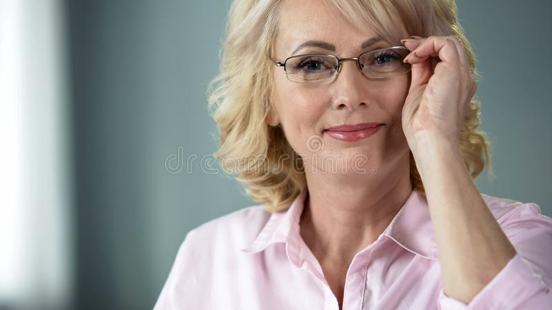 Nice middle-aged woman putting on glasses smiling into camera, healthy eyesight. Stock photo stock photo