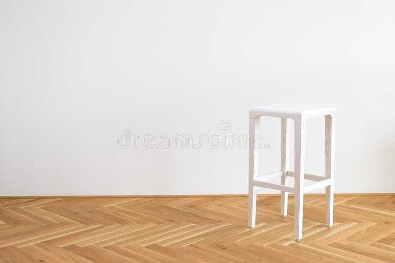 Nice modern simplistic white chair on a wooden floor in front of white background. Modern simplistic white chair on a wooden floor in front of white background royalty free stock photos
