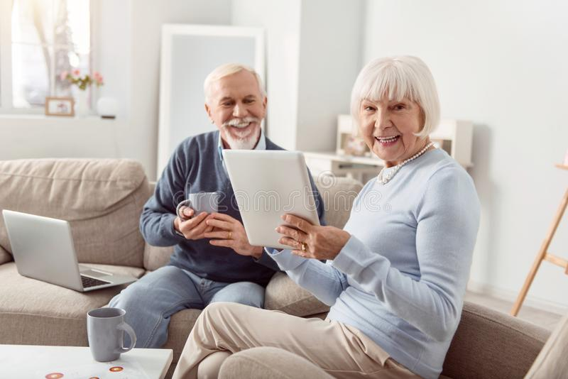 Upbeat senior couple reading social media posts and laughing. Nice morning. Cheerful elderly couple sitting in the living room, reading posts in the social media royalty free stock photos