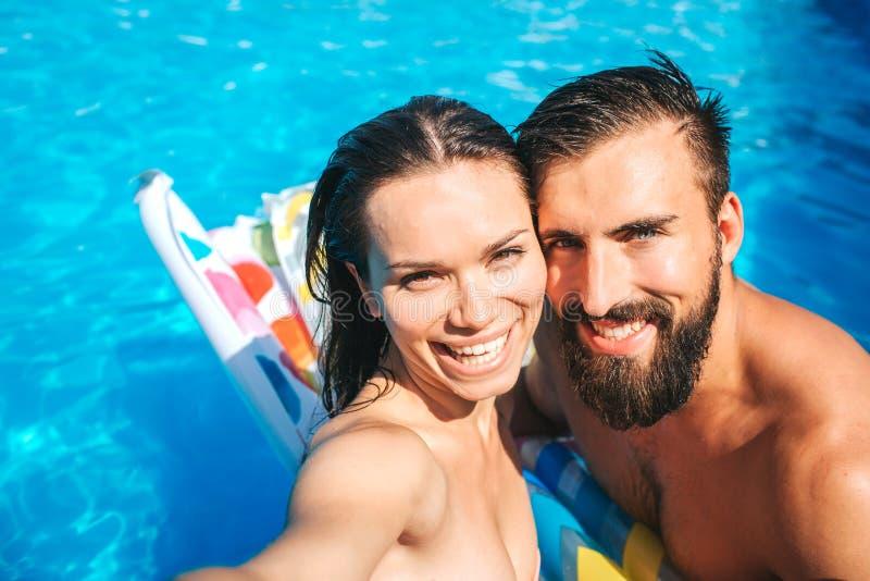 Nice och positiva par som tar selfie och blick på kamera De ler Flickan rymmer kameran De står i simbassäng arkivfoton