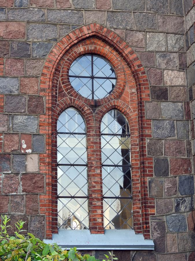 Beautiful old evangelical church window , Lithuania. Nice old evangelical church window and stones wall in Kretinga town stock photography