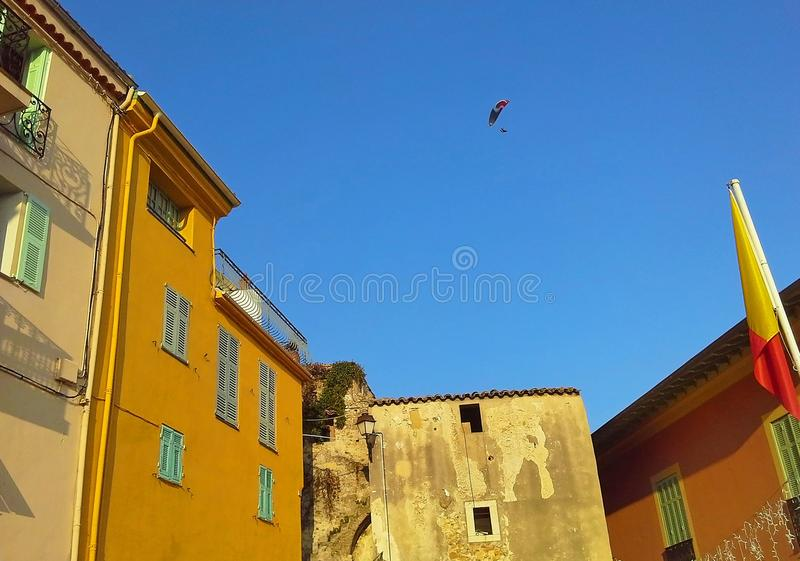 Nice old house, colorful houses, roofs, paragliding in the blue sky. Cote d`Azur, French Riviera, Provence, France.  royalty free stock image