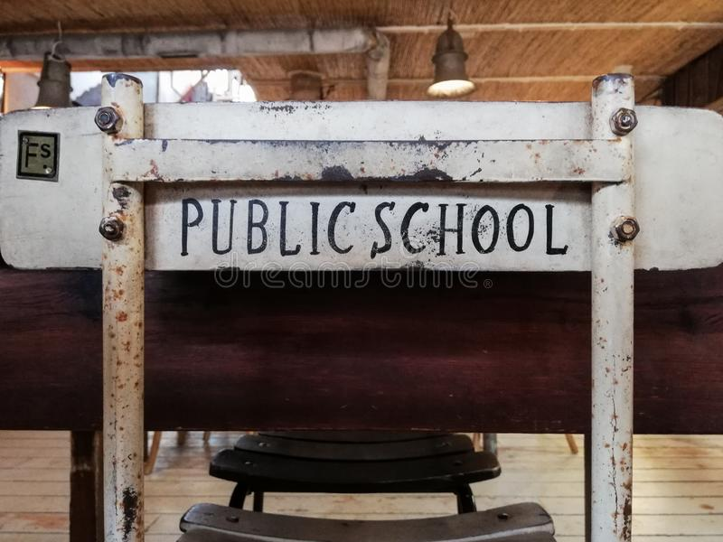 A nice old study chair in front of a desk with the words public school printed on the back royalty free stock image