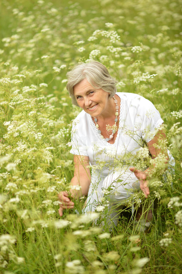 Nice old woman in the middle of the lawn. With white flowers stock photo