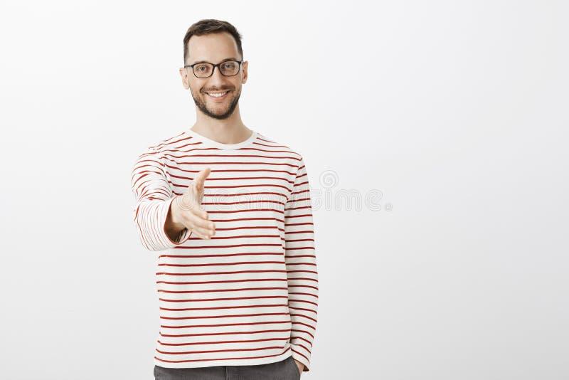Nice om u te ontmoeten Portret die van vriendschappelijke zekere volwassen zakenman in gestreepte trui, hand naar camera binnen t stock afbeelding
