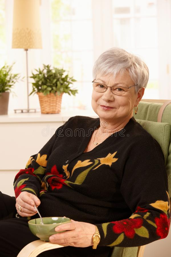 Nice pensioner lady at home. Having tea in bright living room, smiling at camera royalty free stock photos