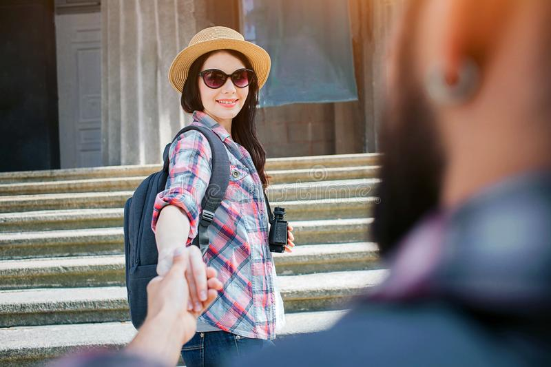 Nice picture of beautiful young woman stand on stair with her boyfriend and look at him. She holds his hand. Woman wears stock photos