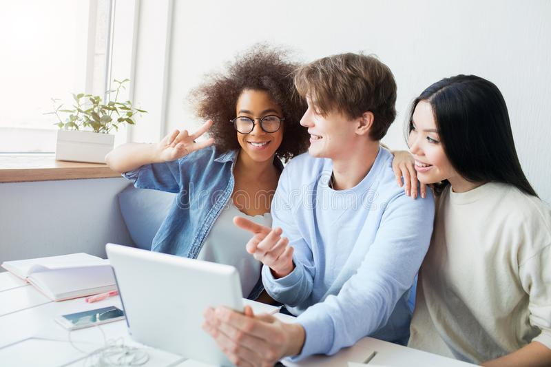 Nice picture of guy holding a tablet and girls talking with somebody using the tablet for that. Asian girl is leaning on. The guy. Afro american girl is showing stock photo