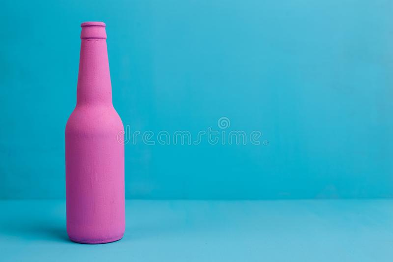 Nice pink beer bottle on blue background. Deceptive attraction o. F alcohol. Alcoholism addiction, alcohol abuse and alcohol dependence concept. Copy space royalty free stock images