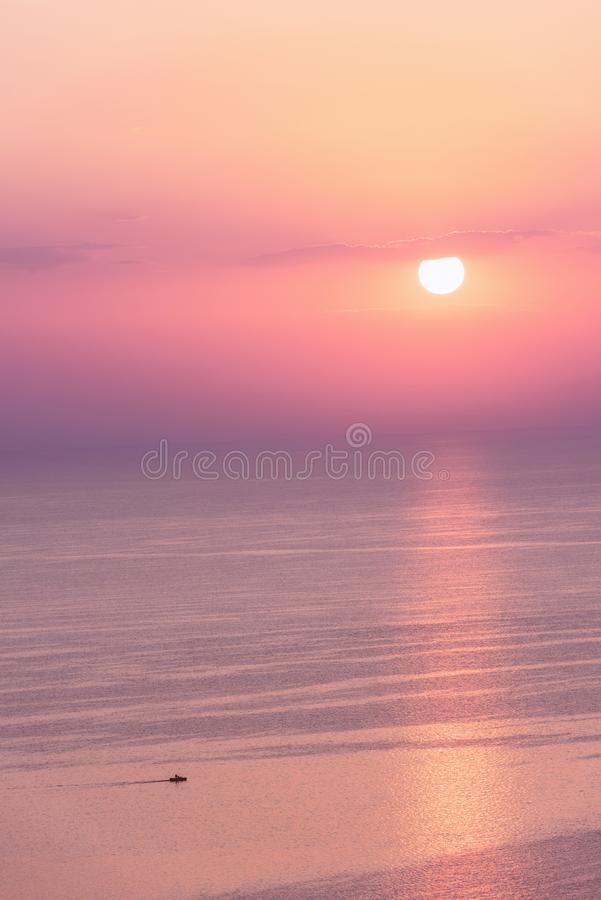 Nice pink sunset seascape in pastel shades, peace and calm outdoor travel background. With copy space, vertical image stock image