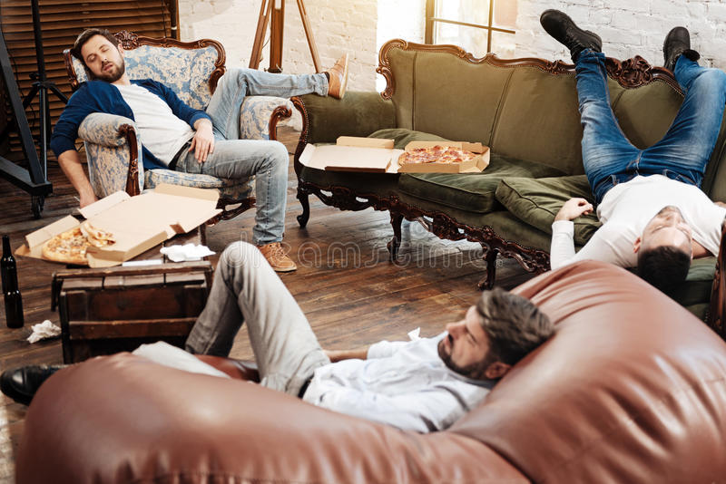 Nice pleasant man lying on the sofa. Comfortable position. Nice pleasant bearded men putting his legs on the back of the sofa and sleeping while lying in the royalty free stock photos