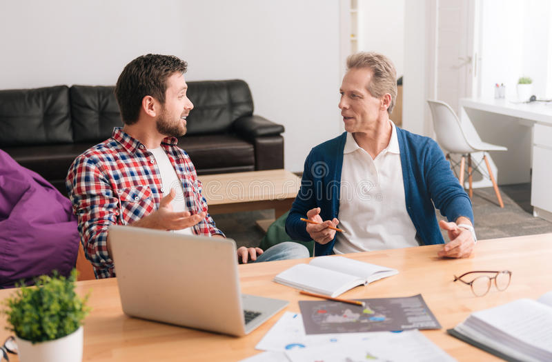 Nice pleasant men looking at each other stock photos
