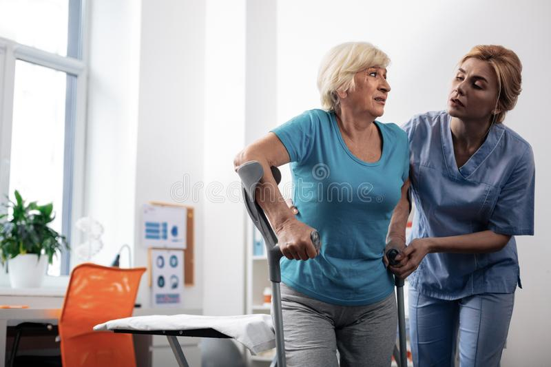 Nice pleasant nurse helping her patients to walk. Do not worry. Nice pleasant nurse standing near her patients while helping her to walk stock images