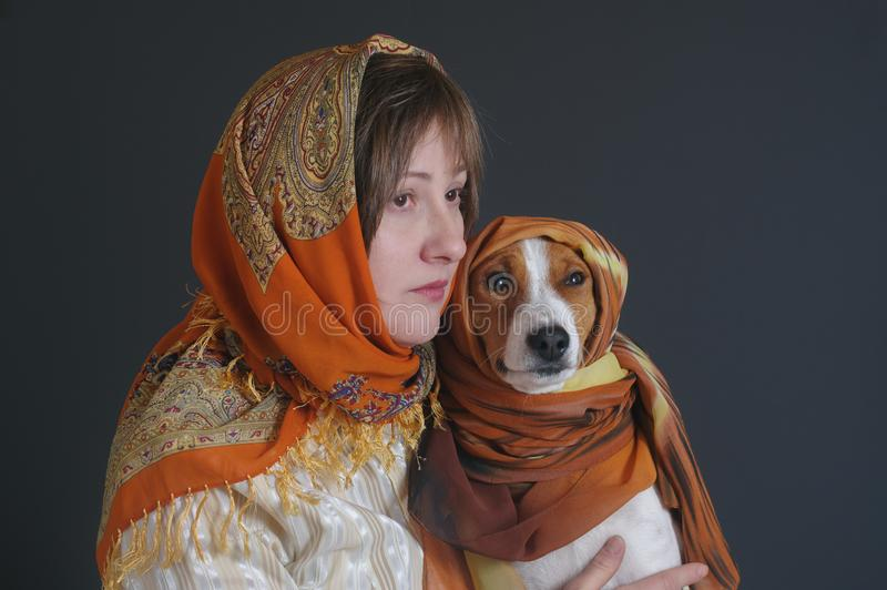 Portrait of beautiful woman with lovely basenji dog both wearing headscarfs royalty free stock images