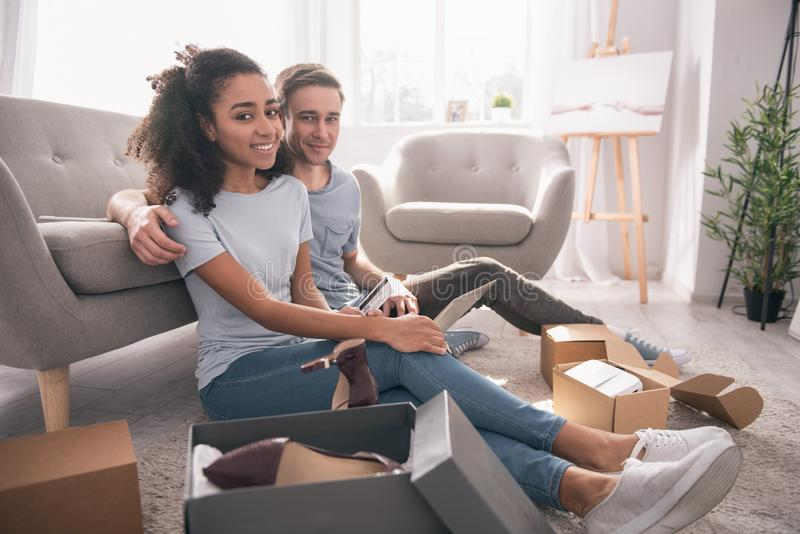 Nice positive couple doing online shopping together stock images