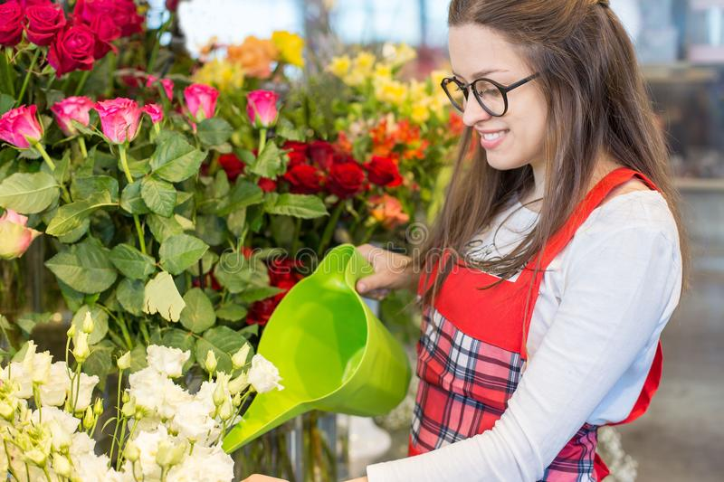 Nice positive flower seller holding water can stock photos