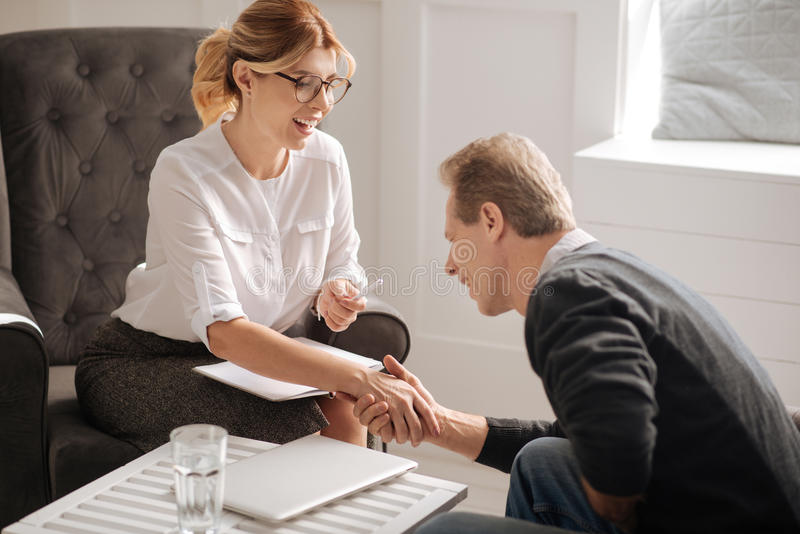Nice positive patient holding the hand of his psychologist stock photography