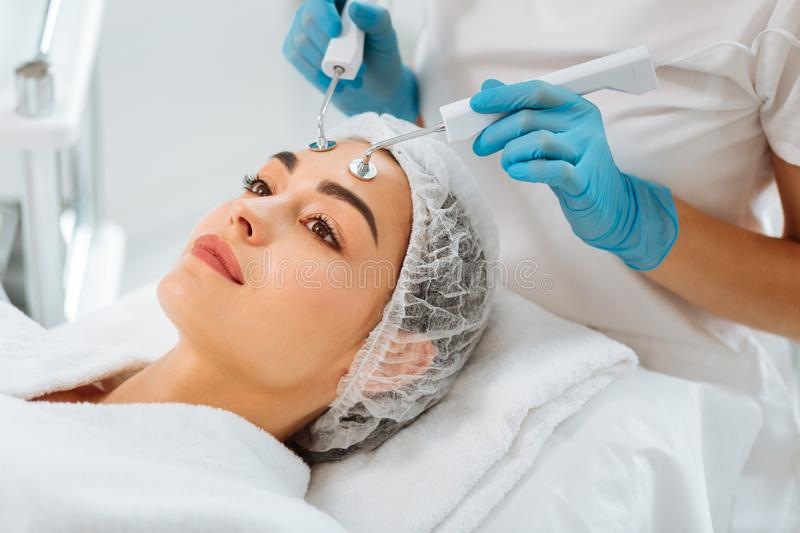 Nice positive woman having microcurrent therapy procedure stock photos