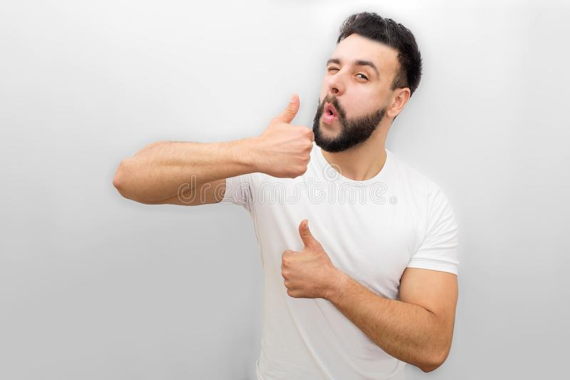 Nice and positive young man stand and winkle on camera. He shows his bog thumbs up. Guy is happy. Isolated on white stock photography