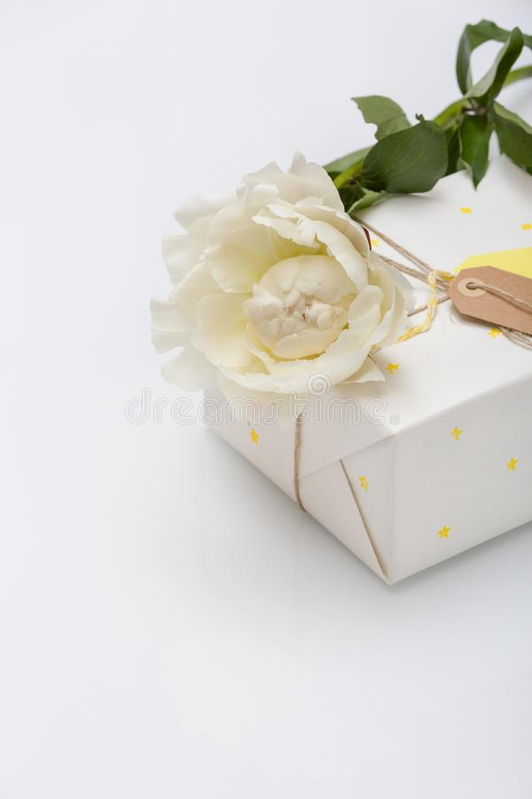 Nice present packed in white paper with small yellow stars with beautiful peony flower on white wooden background. Wrapped gift for birthday party. Mock-up stock photo