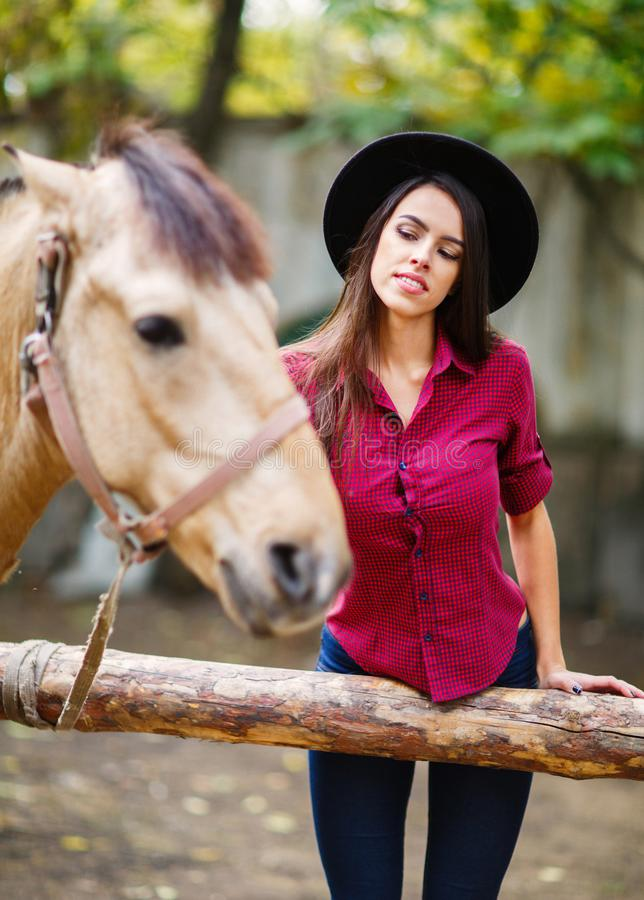 A nice girl in a hat strokes a brown horse. Outside. royalty free stock photography