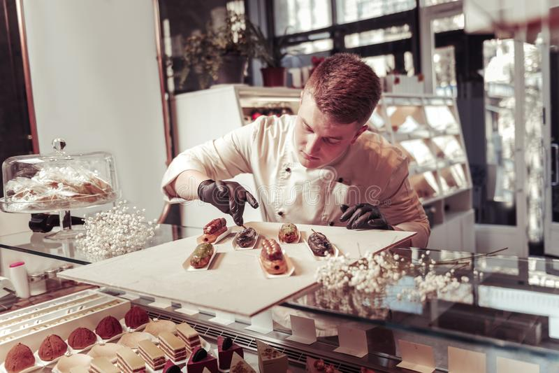 Nice professional confectioner decorating tasty eclairs royalty free stock photo