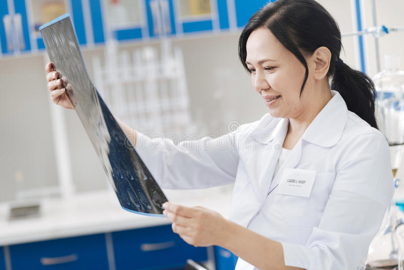 Nice professional doctor looking at the X ray photo. Putting a diagnosis. Nice professional female doctor holding an X ray photo and looking at it while putting royalty free stock photo