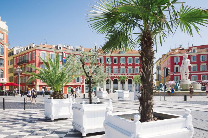 Nice, Provance, Alpes, Cote d`Azur, French  July 31, 2018; Square Massena with red building and alley of potted trees. royalty free stock photography