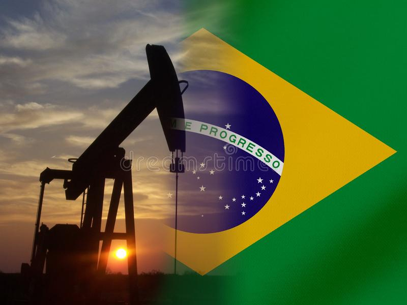 Nice pumpjack oil extraction and cloudy sky in sunset with the Brasil flag royalty free stock images