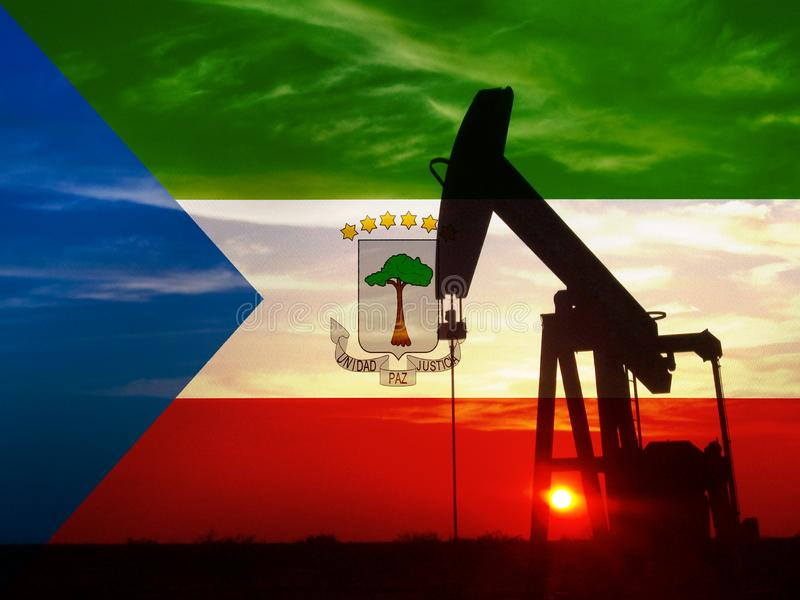 Nice pumpjack oil extraction and cloudy sky in sunset with the Equatorial Guinea flag.  stock photos