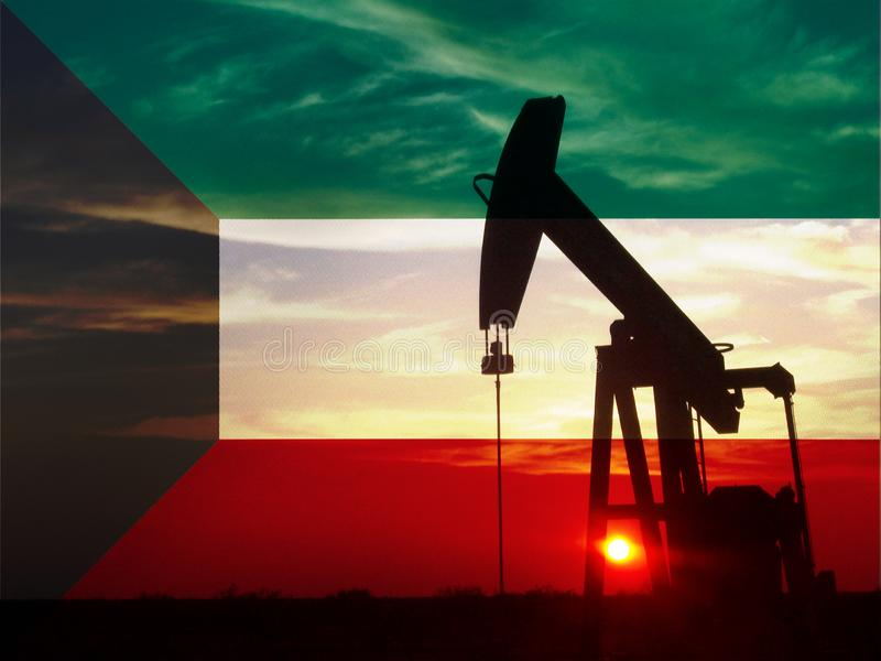 Nice pumpjack oil extraction and cloudy sky in sunset with the Kuwait flag stock photo