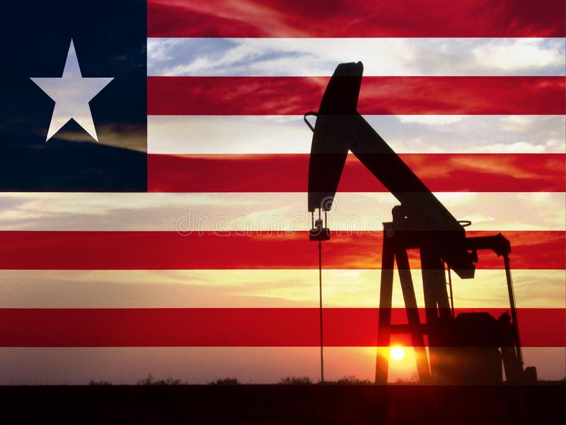 Nice pumpjack oil extraction and cloudy sky in sunset with the  Liberia flag royalty free stock photos