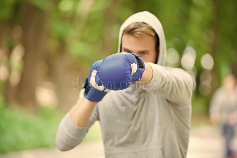 Nice punch. Boxing training endurance. Man athlete concentrated face with sport gloves practicing boxing nature. Background. Boxer ready to fight. Sportsman royalty free stock photography