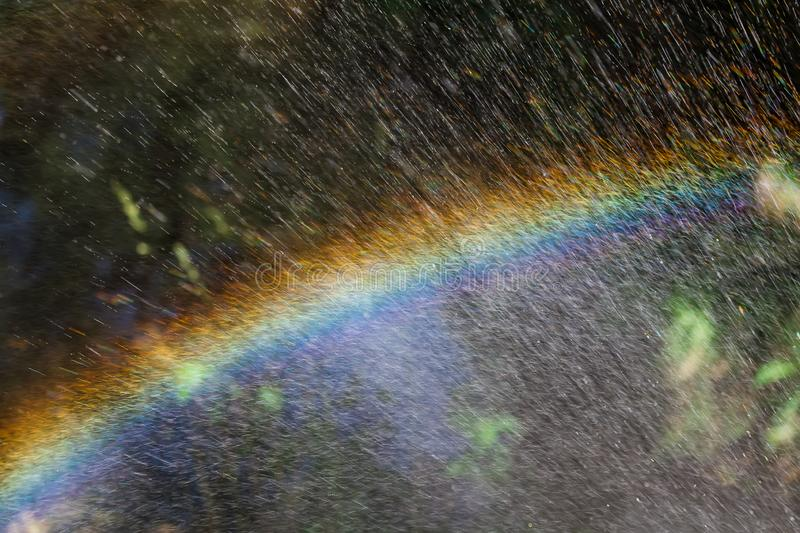 Nice rainbow on splash water, abstract shape, close up photo, copy space stock photography