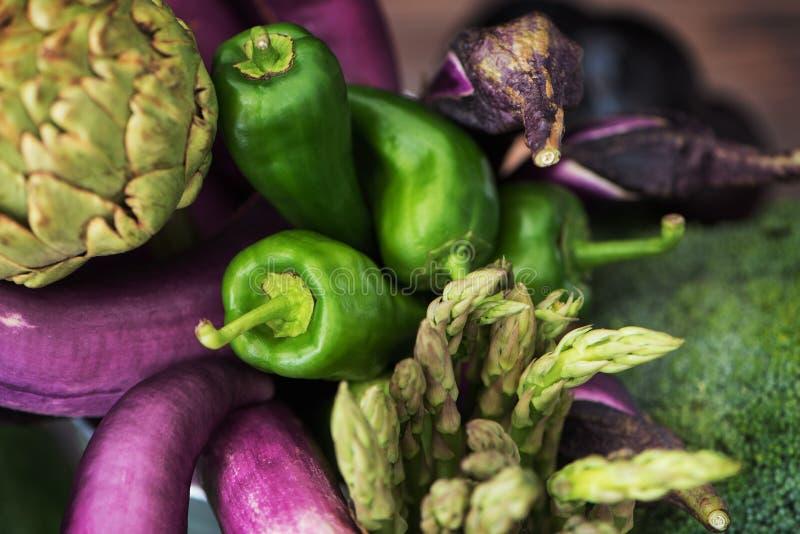 Nice raw vegetable still life of thin purple eggplants, green paprika peppers, plumps, artichoke, brocoli and asparagus. Fresh foo royalty free stock image