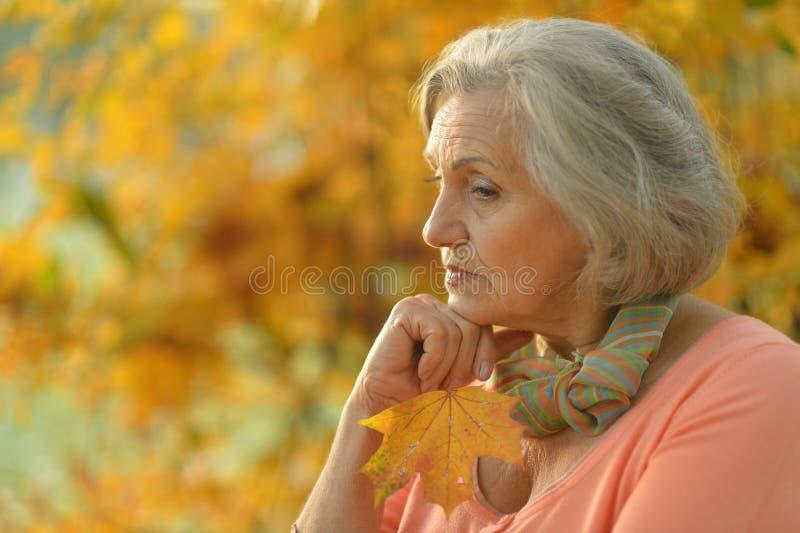 Nice sad old woman. On the autumn background stock image