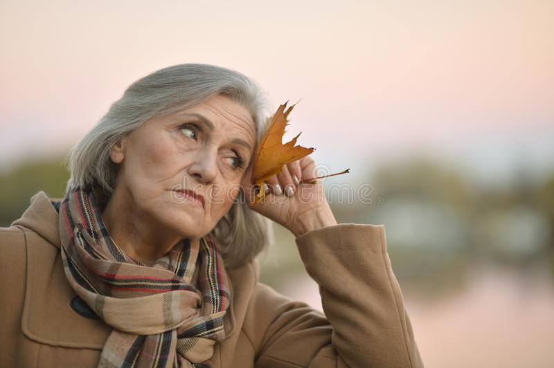 Nice sad old woman. On the autumn background royalty free stock image