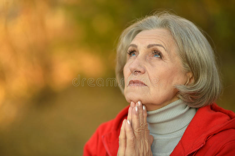 Nice sad old woman. On the autumn background royalty free stock images