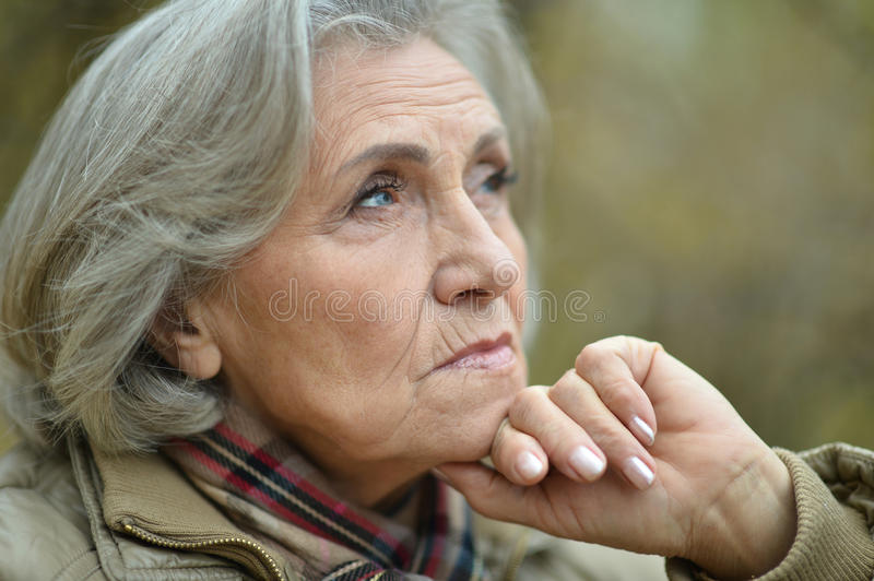 Nice sad old woman. On the autumn background stock photography
